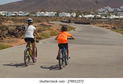 PLAYA BLANCA, LANZAROTE, SPAIN - MAY 10, 2015: Holiday makers cycling towards Playa Blanca on promenade.