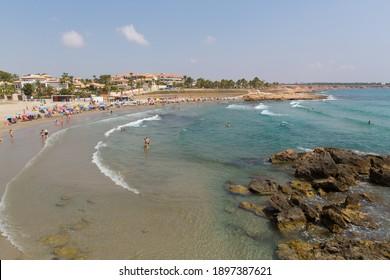 PLAYA CALA ESTACA, LA ZENIA, SPAIN-JULY 1st 2019: Beautiful summer weather attracted holidaymakers to Playa Cala Estaca beach, Playa Flamenca,  Costa Blanca, Spain, Monday 1st July 2019