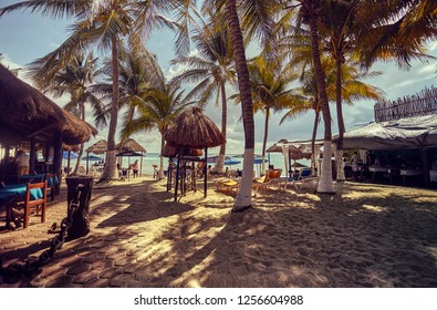 PLAYA DEL CARMEN, MEXICO - DECEMBER 10, 2018: View of a glimpse of Playa del Carmen beach in Mexico, full of palm trees and with some bar huts.
