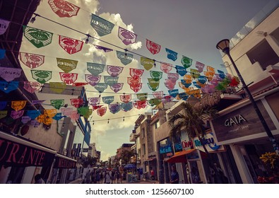 PLAYA DEL CARMEN, MEXICO - DECEMBER 10, 2018:  Colored flags hanging at the ends of two buildings inside one of the main streets of Playa del Carmen in Mexico.