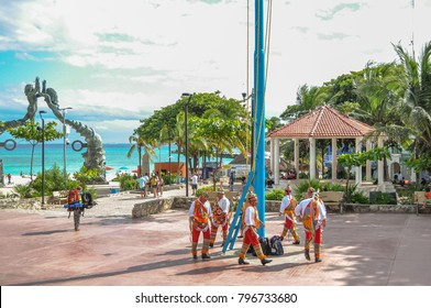 PLAYA DEL CARMEN, MEXICO - DECEMBER 13, 2017: The Voladores of Papantla dressed in traditional clothing perform for tourists in Mexican park with ocean in the background