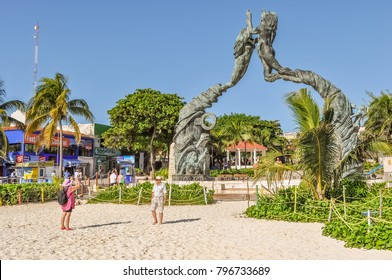 PLAYA DEL CARMEN, MEXICO - DECEMBER 13, 2017: Senior tourists taking photos in front of Portal Maya Statue designed by artist Arturo Taravez  in Parque Fundadores in Playa del Carmen