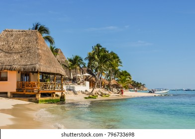 PLAYA DEL CARMEN, MEXICO - DECEMBER 12, 2017: Resort beach cabins on a Mexican beach with palms by the turquoise ocean