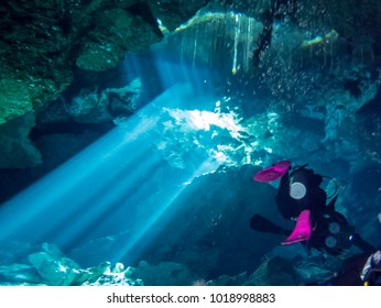 Playa del Carmen, Mexico - february 2017 : in the cenote Chac Mool the divers approach the exit of the cave from where the sun enters forming fantastic play of light