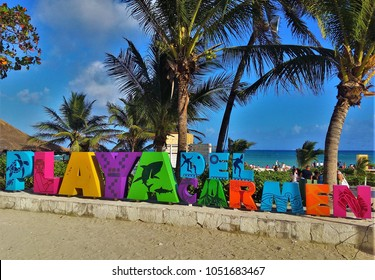 PLAYA DEL CARMEN, MEXICO – FEBRUARY 2018: Colorful sign Playa del Carmen in city of same name on Riviera Maya in Yucatan, Mexico, with coconut palms, turquoise sea and blue sky in background