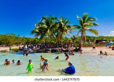 Playa del Carmen, Mexico - February 10 2019: Tropical paradise in the Caribbean Sea in Mexico with white beaches and palm trees in the blue sea