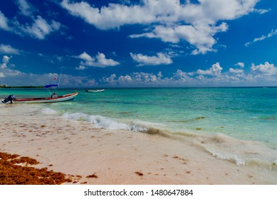 Playa del Carmen, Mexico - February 20 2019: Caribbean beach equipped with colorful chairs and umbrellas under the Caribbean palm trees