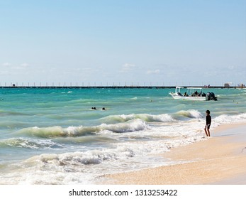 Playa del Carmen, Mexico - January 5 2016 - People on the beach in Playa del Carmen. The city boasts a wide array of tourist activities due to its geographical location in the Riviera Maya.