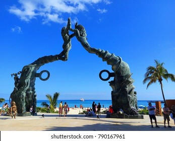 PLAYA DEL CARMEN, MEXICO – JANUARY, 2018: View of Portal Maya, iconic sculpture landmark of Playa del Carmen with beach, Caribbean Sea and ferry to Cozumel in background, Riviera Maya, Mexico