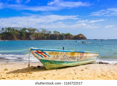 PLAYA MONTEZUMA, COSTA RICA, JUNE, 28, 2018: Outdoor view of small boat in the shore in Playa Montezuma during gorgeous sunny day with blue sky and blue water