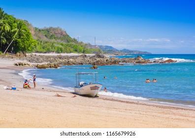 PLAYA MOTEZUMA, COSTA RICA, JUNE, 28, 2018: Unidentified people swimming and enjoying the beautiful blue water of the beach in Playa Montezuma