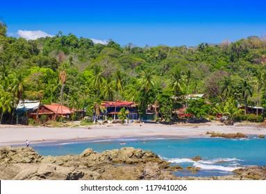PLAYA MOTEZUMA, COSTA RICA, JUNE, 28, 2018: Unidentified people swimming and enjoying the beautiful blue water in the rocky beach in Playa Montezuma