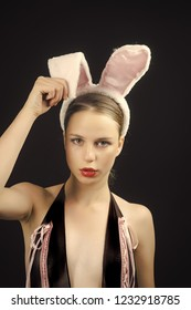 Playboy girl posing on black background. Woman with red lips wearing rabbit ears. Sexy bunny model. Easter holiday concept.