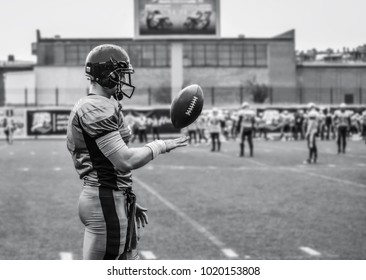 The player of the American football team is throwing the ball with his hand.