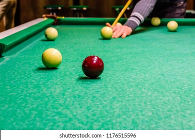 Player arm with the cue and balls on a green cloth. Russian billiard
