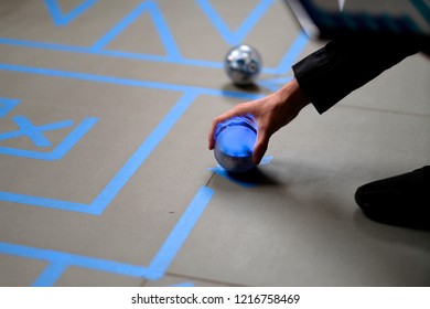 Player arm with a robot ball at the beginning of a maze