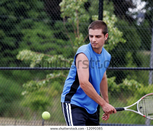 Player concentrates on the tennis ball while preparing to hit a backhand