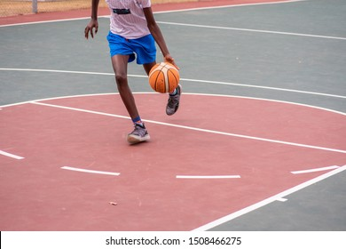 Player dribbling basketball towards the hoop