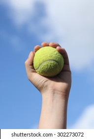 Player Gripping a Yellow Tennis Ball Against a Blue Sky