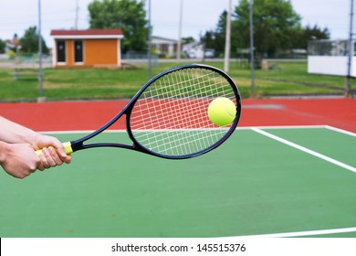 Player hands on tennis racket hitting a back hand volley