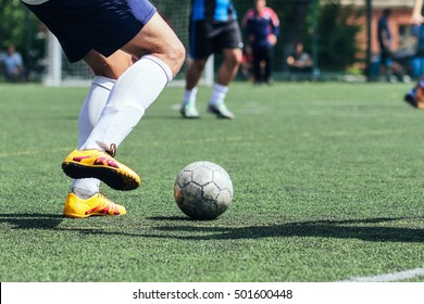 A player hits the ball on the artificial turf. Football / Soccer.