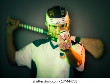 Player Holding Hurling Ball. A hurling player holds a ball in front of his face holding the stick on his shoulders. shallow depth of field. green and orange light. focus on ball,