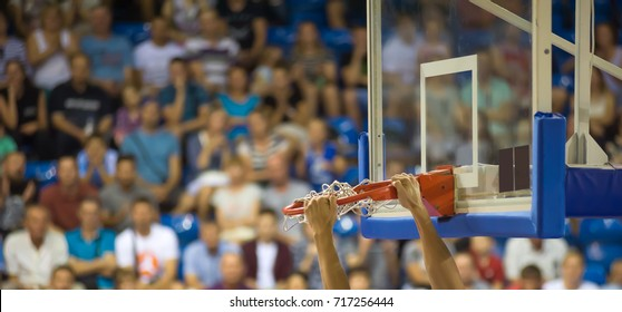 The player holds his hands to the basketball ring. In the background in the stands are fans