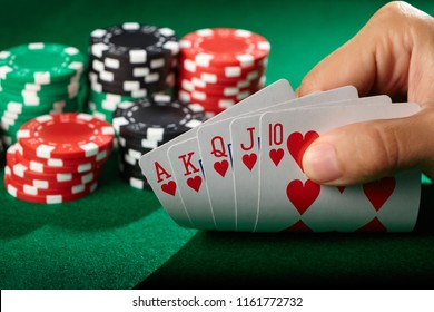 Player looking at cards. Winning poker hand royal flush.