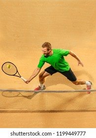 Player lunge, game of defense. The one caucasian fit man playing tennis at the earthen court . Player jumping in full length with racquet and ball. Emotions on face. Upper