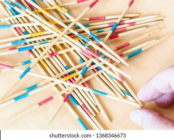 player picks up a stick from pile in Mikado game close up on wood board