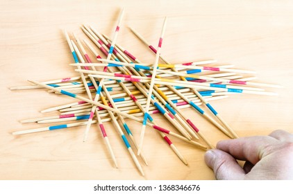 player picks up a stick from pile in Mikado game on wooden board