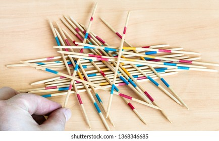 player picks up a stick from pile in Mikado pick-up sticks game on wood board
