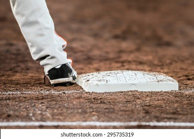 Player waiting with hes feet touching the base plate infield during a baseball match. The baseball player wears black shoes touching the white baseplate laying in brown dirt.