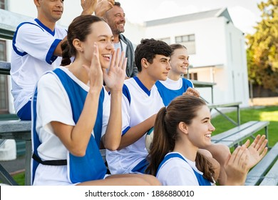 Players cheering for school football team sitting on stands. High school guys and girls clapping hands while watching sport match. Group of fans watching a sports event at stadium while encouraging.