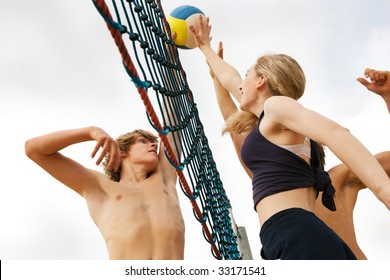 Players trying to block a dangerous attack in a beach volleyball game