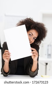 Playful African American businesswoman peeking around a blank sheet of paper with a mischievous look