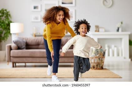 Playful african american mother trying to catch excited small child son while playing together at home, playful mom and kid running and having fun in living room. Happy family enjoying leisure time