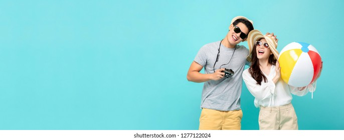Playful Asian couple in summer casual clothes with beach accessories studio shot isolated on light blue banner background with copy space