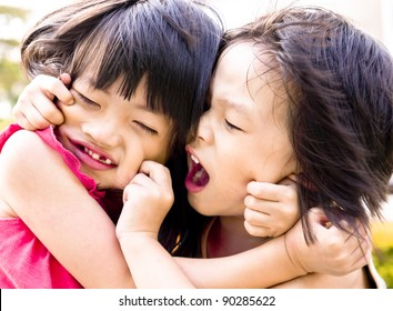 Playful Asian siblings pulling each other faces.