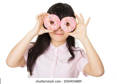 Playful Asian woman having some fun with delicious strawberry frosted donuts