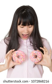 Playful Asian woman having some fun with delicious strawberry frosted donuts isolated on a white background