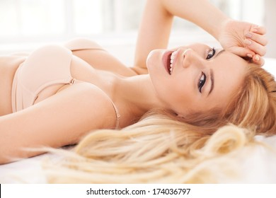 Playful and beautiful. Side view of cheerful and attractive young woman in lingerie lying in bed and smiling at camera