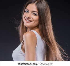 Playful beauty. Playful young brown hair woman in tank top holding hands in hair while standing against dark background.