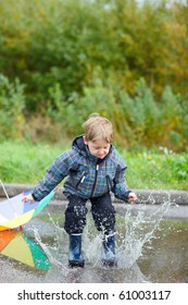 Playful boy jumping in puddle on rainy autumn day