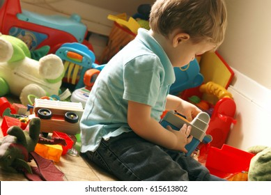 A playful boy toddler of almost two years of age enjoys the toys in the toy room.