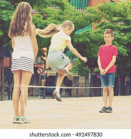 Playful boy and two girls skipping on elastic jumping rope in playground in park
