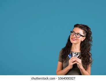Playful brunette woman is thinking of online shopping in internet holding many credit cards