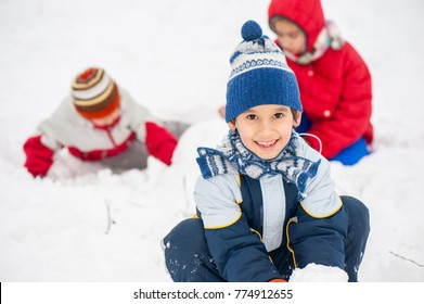 Playful cheerful children sledding and making snowman in snow