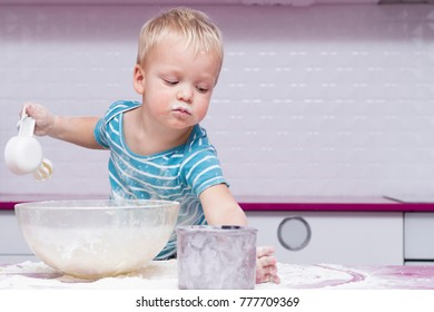 Playful child boy with kitchenware and foodstuffs making pastry.