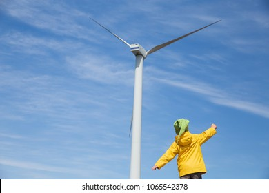 playful child looks at the wind turbine. Little kid in front of windmill. copy space for your text